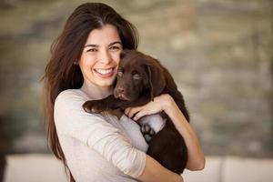 en leende brunettdam som håller en brun hund foto