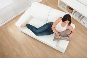 ung kvinna med digital tablet på soffan foto