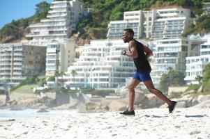 fit ung man springer på stranden foto