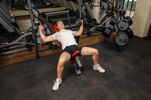 ung man gör hantel lutning bänkpress träning i gymmet