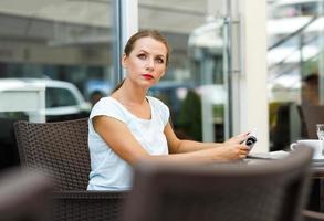 attraktiv ung kvinna läser en tidning som sitter på caféet foto