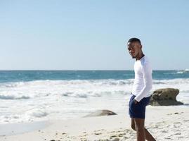 stilig ung man som står ensam på stranden foto