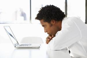 affärsman i office stirrar på bärbar datortänkande foto