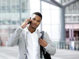 cool ung man med väska som pratar i mobiltelefon foto