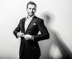 elegant ung stilig man i klassisk svart kostym. foto
