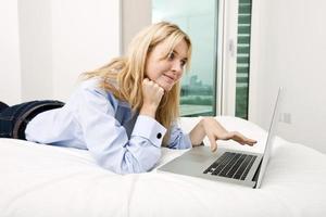 ung affärskvinna som använder laptop medan du ligger i sängen foto