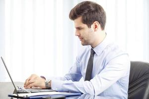porträtt av ung affärsman med laptop foto