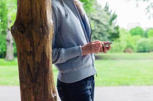 kvinna som använder sin smartphone i parken foto