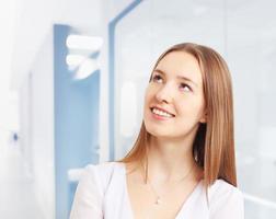 bild av vacker kvinna som ler medan man tänker på kontoret foto