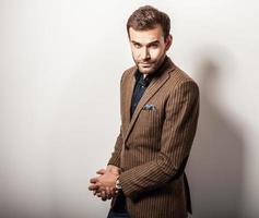 elegant ung stilig man i lyxdräkt. studio mode porträtt. foto
