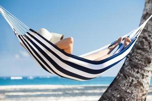kvinna i hängmatta på stranden foto