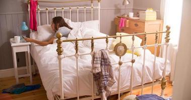 kvinna i sängen väckt av larm på mobiltelefonen foto