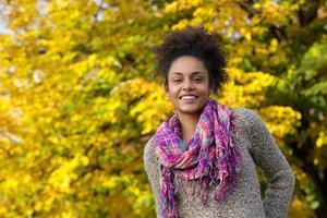 vacker ung svart kvinna som ler utomhus på hösten foto