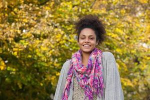 ung afrikansk amerikansk kvinna som står utomhus på hösten foto