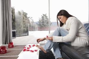 kvinna som målar tånaglar i vardagsrummet
