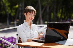 ung affärskvinna med laptop på ett trottoarkafé foto