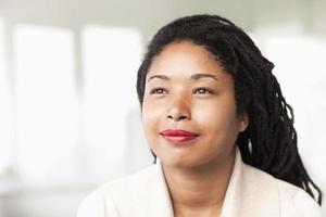 porträtt av leende affärskvinna med dreadlocks, huvud och axlar foto