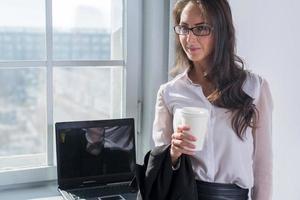 ung kvinna i glas med koppen kaffe eller foto