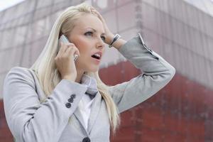 närbild av chockad affärskvinna i mobiltelefon mot kontorsbyggnad foto