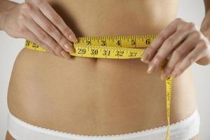 närbild av kvinna i underkläder mäta midjan med tejp foto