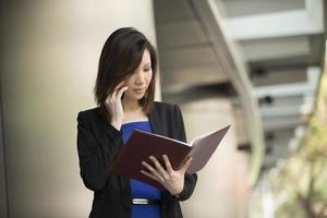 asiatisk affärskvinna som står utanför med telefon