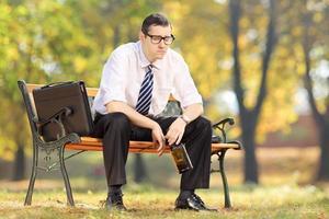 besviken affärsman som sitter på en träbänk, i park foto