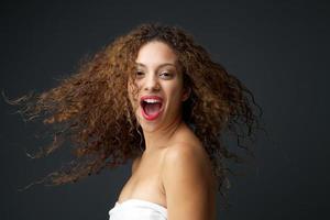 porträtt av en vacker ung kvinna med blåser hår skrattar