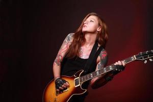 attraktiv tjej med många tatueringar som spelar elgitarr foto