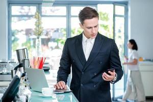 uppringning. säker och framgångsrik affärsman som står på ett kontor foto