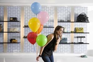 glad ung kvinna i butiker som håller ballonger foto