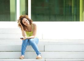 kvinna sitter utanför med hörlurar foto