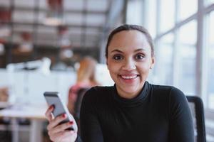 afrikansk kvinna på jobbet tittar på leende kamera
