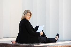 ung affärskvinna med en mapp som sitter vid väggen foto