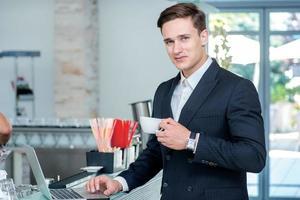 kaffepaus. säker och framgångsrik affärsman leende foto