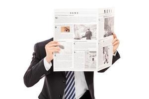 lömsk chef som kikar genom ett hål i tidningen foto