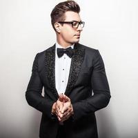 elegant ung stilig man i svart lyxdräkt. foto