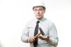 ingenjör i vit hjälm med hammare i handen foto