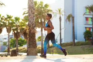 sportig svart kvinna som kör i park foto