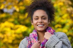 attraktiv ung afrikansk amerikansk kvinna som ler på hösten