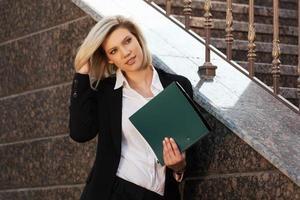ung affärskvinna med en mapp mot kontorsbyggnad foto