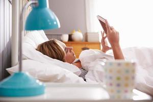 kvinna i sängen tittar på digital tablet foto