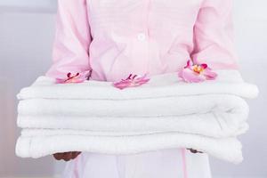 hushållerska som bär handdukar på hotellet foto