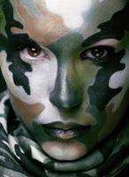 kvinna med militär stilkläder och ansiktsmålsmink foto