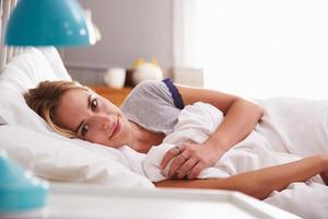 porträtt av ung kvinna som ligger i sängen foto