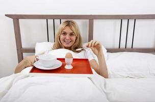 porträtt av ung kvinna med frukostbricka i sängen foto