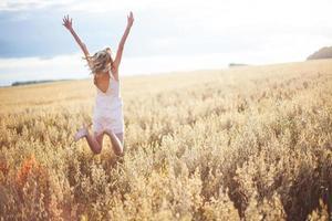 kvinna i vetefält med utsträckta armar foto