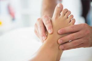 närbild av fysioterapeut som masserar patientens fot foto