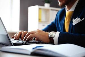 stilig affärsman som arbetar med bärbar dator i office foto