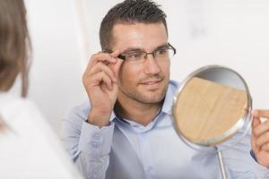 man försöker nya glasögon med ögonläkare foto