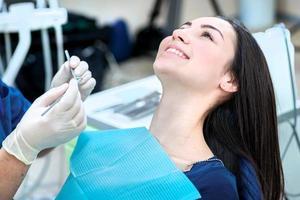 leende patient sitter i en tandläkerstol. patientens tandläkare foto